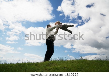 father and daughter play on a meadow