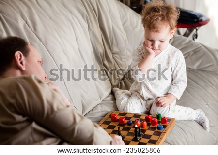 Father and daughter playing chess - stock photo