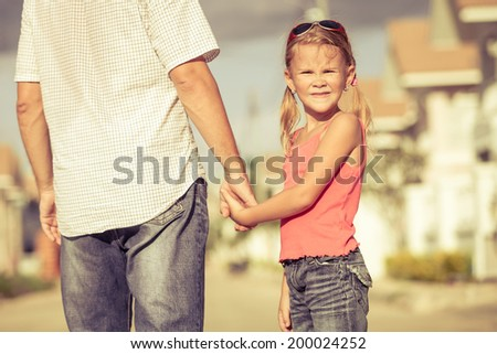 father and daughter playing near a house at the day time - stock photo