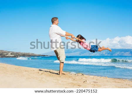 Father and Daughter Playing on the Beach - stock photo
