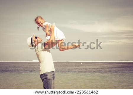father and daughter playing on the beach at the day time - stock photo