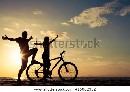 Father and daughter  playing on the beach at the sunset time. Concept of friendly family. - stock photo