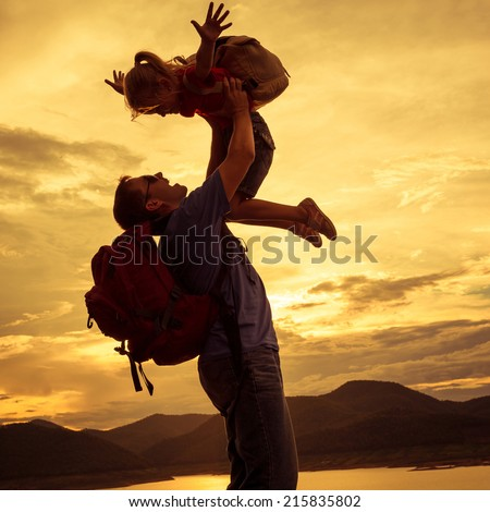 father and daughter playing on the coast of lake in the mountains of at the sunset time - stock photo