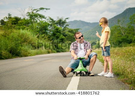 Father and daughter playing  on the road at the day time.  Concept of friendly family. - stock photo