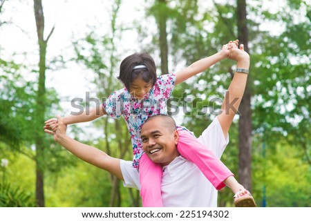 Father and daughter playing piggy back at outdoor garden park. Happy Southeast Asian family living lifestyle. - stock photo