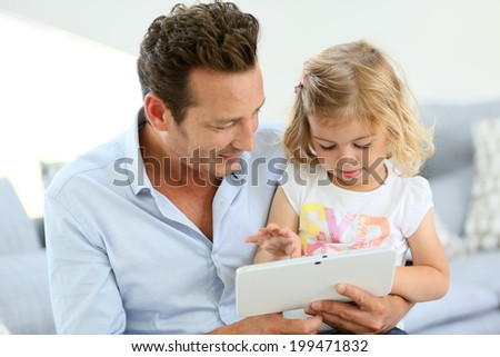 Father and daughter playing with digital tablet - stock photo