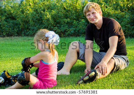 Father and daughter putting on roller skates - stock photo