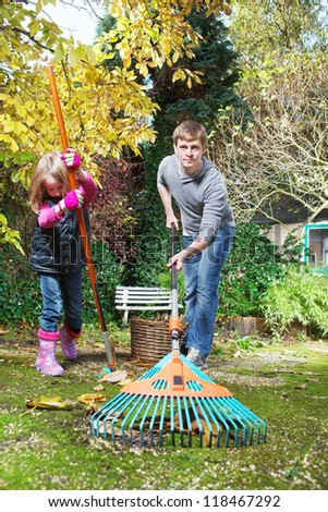 Father and daughter raking autumn leaves in the backyard - stock photo