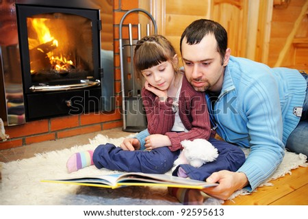 Father and daughter reading a book in front of fireplace - stock photo