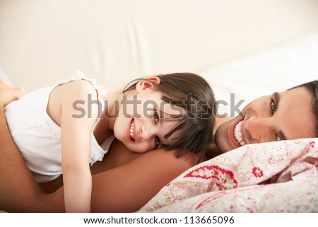 Father And Daughter Relaxing Together In Bed - stock photo