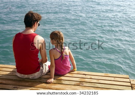 father and daughter sitting on pier looking on sea - stock photo