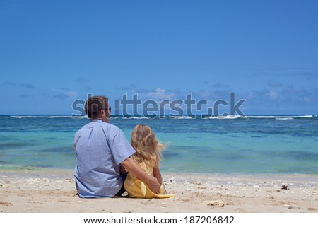 father and daughter sitting on the beach in the day time - stock photo