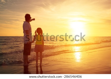 father and daughter standing on the beach watching sunset - stock photo