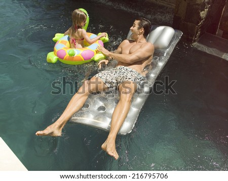 Father and daughter swimming. - stock photo