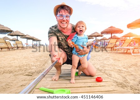 Father and daughter taking selfie on the beach - Cheerful dad and child playing outdoor on summer vacation day - Concept of family fun  moment using technology self photo for holiday joyful memories  - stock photo