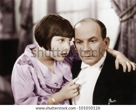 Father and daughter talking to each other in a living room - stock photo