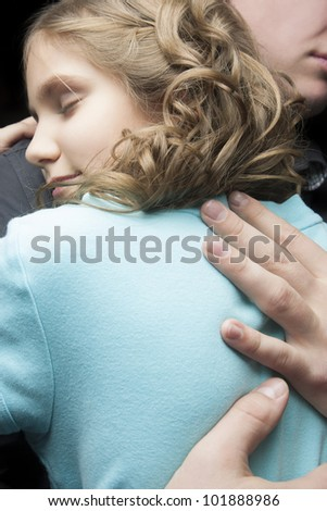 father and daughter together embracing over black background - stock photo
