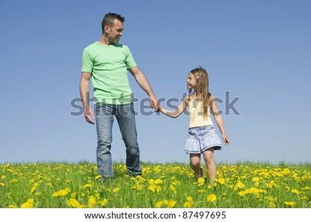 Father and daughter together on meadow - stock photo
