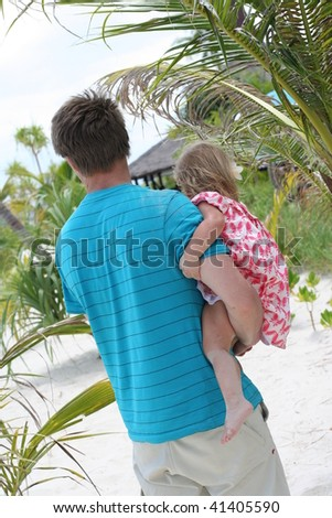 Father and daughter walking on the beach - stock photo