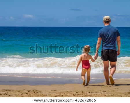 Father and daughter walking together on the beach during summer holidays - stock photo