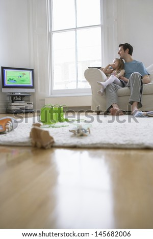 Father and daughter watching television in the living room at home - stock photo