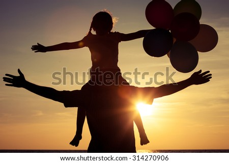 Father and daughter with balloons playing on the beach at the sunset time. Concept of friendly family. - stock photo