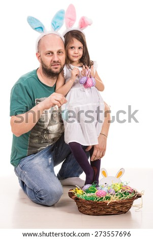 Father and daughter with bunny ears holding Easter eggs - stock photo