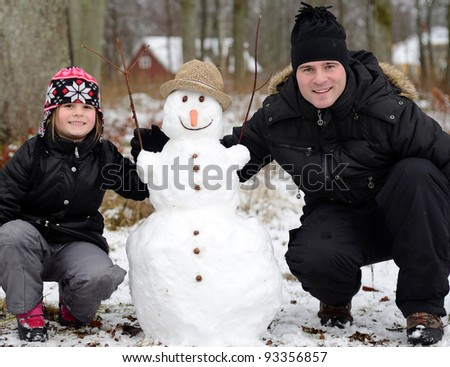 Father and daughter with snowman - stock photo