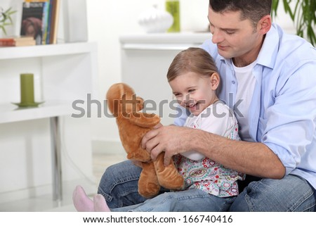 Father and daughter with teddy - stock photo
