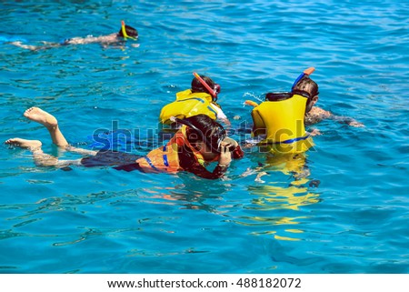 Father and daughters enjoy snorkelling in a tropical sea at Nusa, Bali, Indonesia