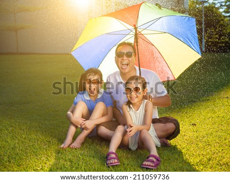 Father and daughters sitting on a meadow with colorful umbrella - stock photo