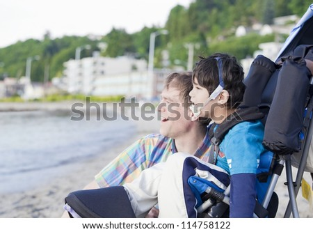 Father and disabled five year old son  on beach, looking out over water - stock photo