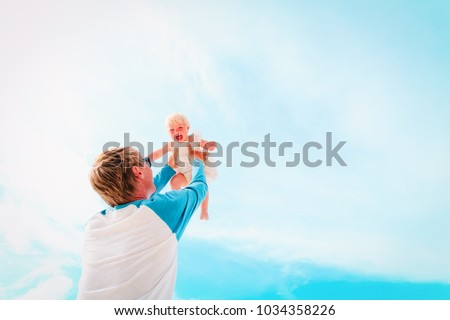 father and happy little daughter play at sky