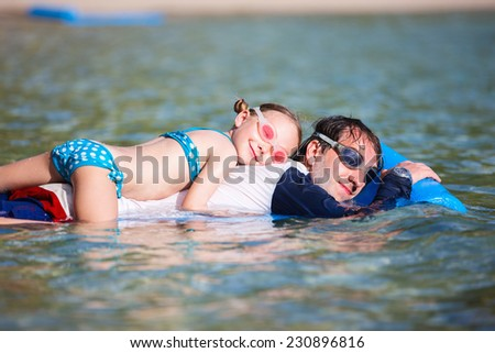 Father and his adorable little daughter on beach vacation relaxing on floating mat