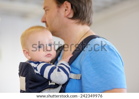 Father and his baby boy in a baby carrier  - stock photo
