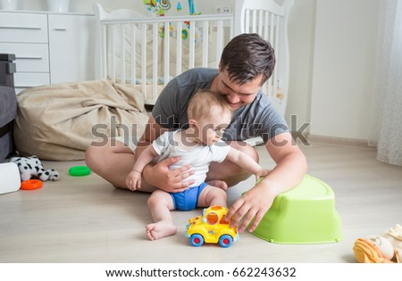Father and his baby boy playing with toy car on floor at home