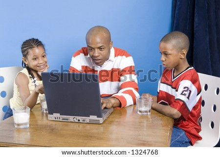 Father and his children play with PC - stock photo
