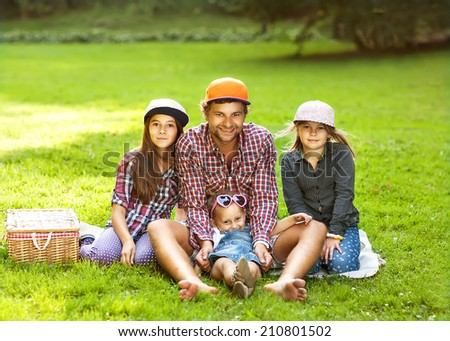 Father and his 3 daughters lie on the grass in sunglasses happy. hipster Style - stock photo