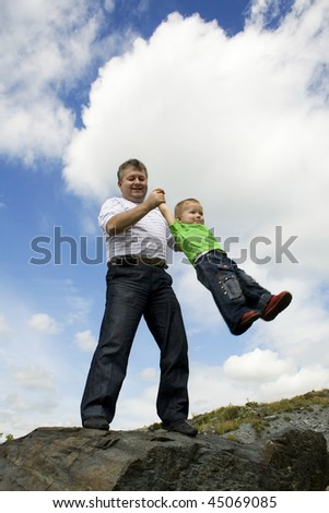 Father and his flying son. Against the background sky and the clouds.