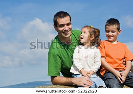 Father and his happy children sitting on the stone