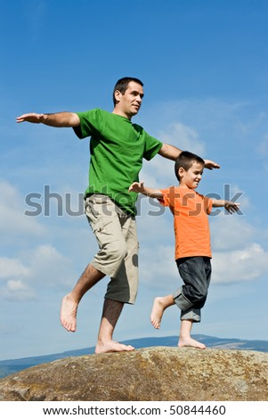 Father and his happy son staying on the stone with lifted legs and balancing - stock photo