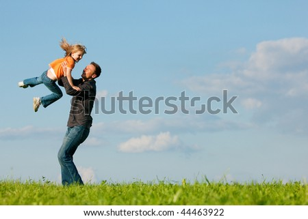 Father and his kid - daughter - playing together at a meadow, he is throwing her into the air at a late summer afternoon, family concept
