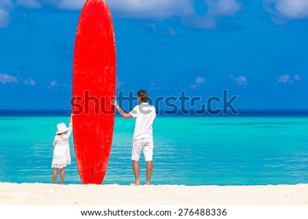 Father and his kid with surfboard during summer vacation