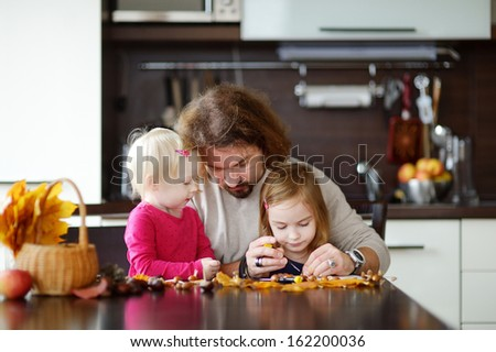 Father and his kids making chestnuts creatures together - stock photo