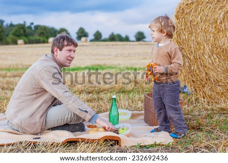 Father and his little cute kid son having picnic on wheat field on late summer day, outdoors. Family concept. - stock photo