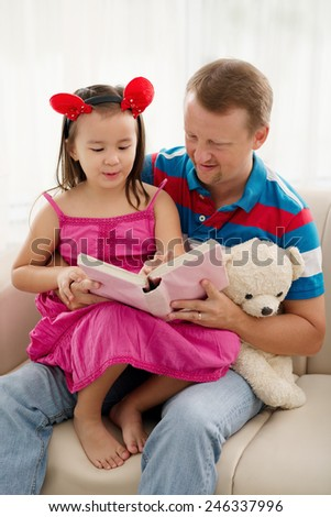 Father and his little daughter reading a book together