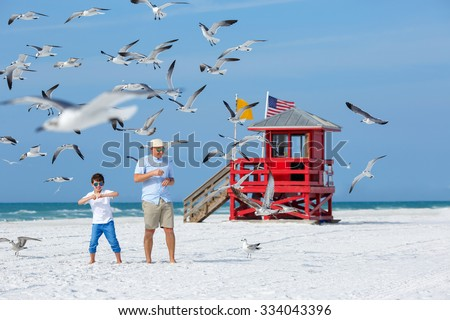 Father and his little son feeding seagulls on tropical beach, Florida summer holiday vacation - stock photo