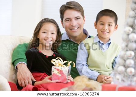 Father And His Son And Daughter Sitting On Sofa,Holding A Christmas Present - stock photo