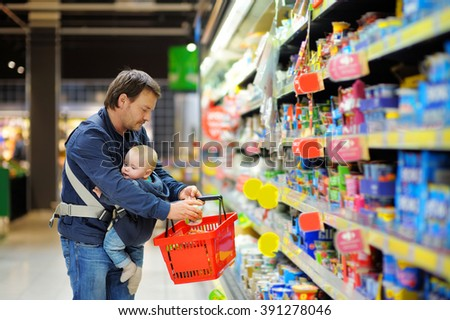 Father and his son at supermarket together - stock photo