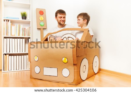 Father and his son driving handmade cardboard car - stock photo